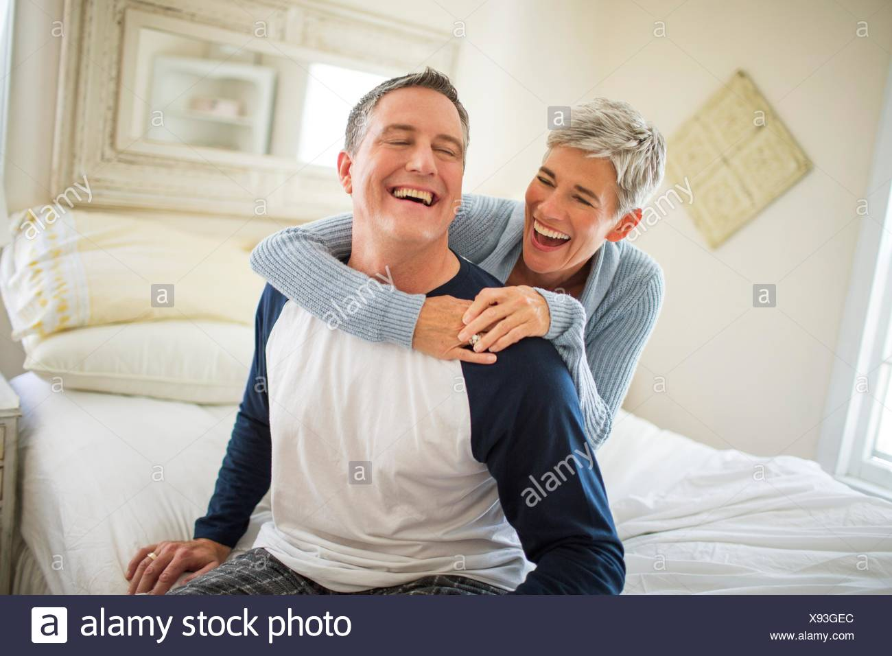 Mature couple laughing and fooling around on bed - Stock Image