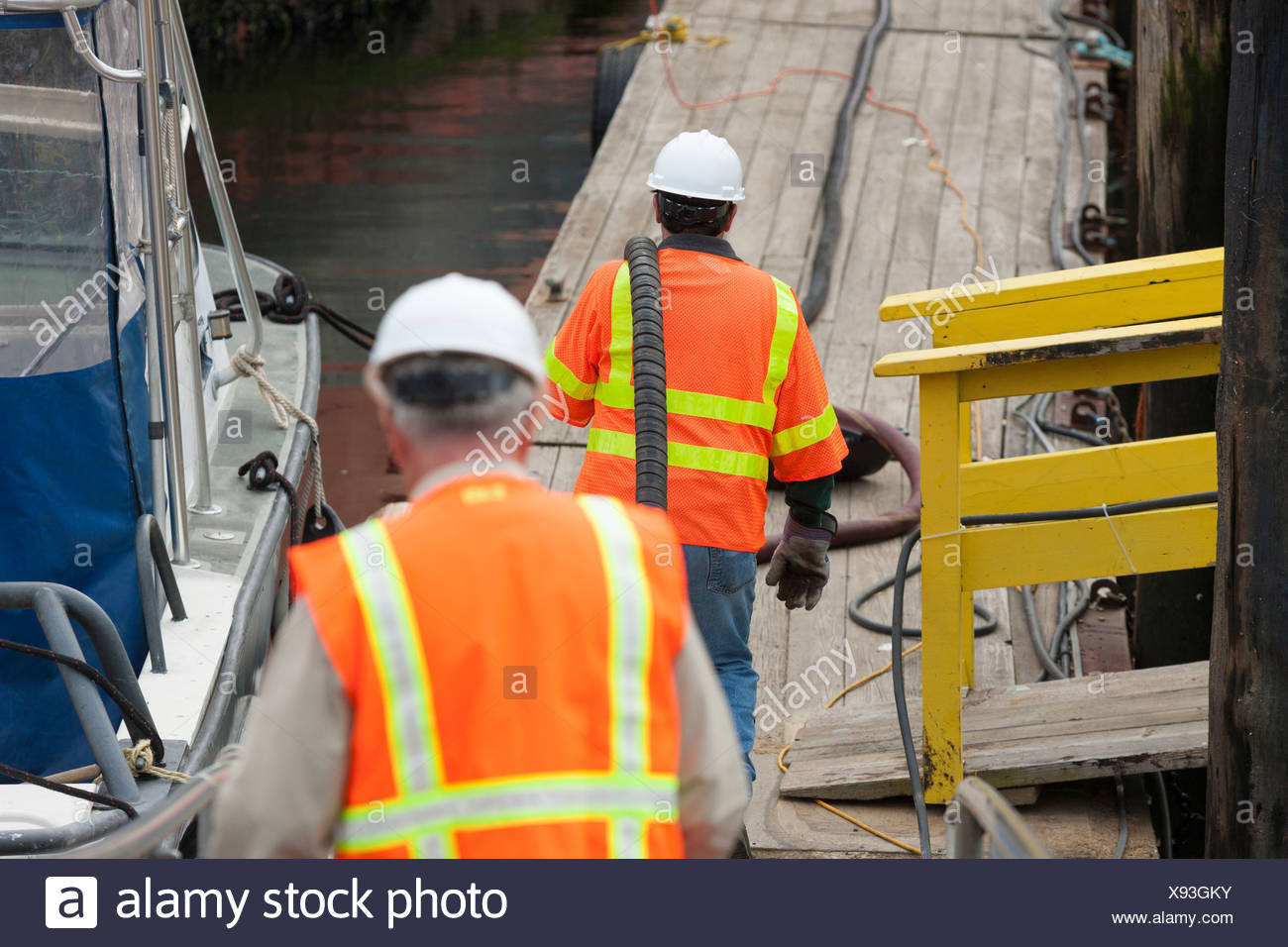 Environmental engineers extending petroleum hose for toxic waste cleanup to commercial ship - Stock Image
