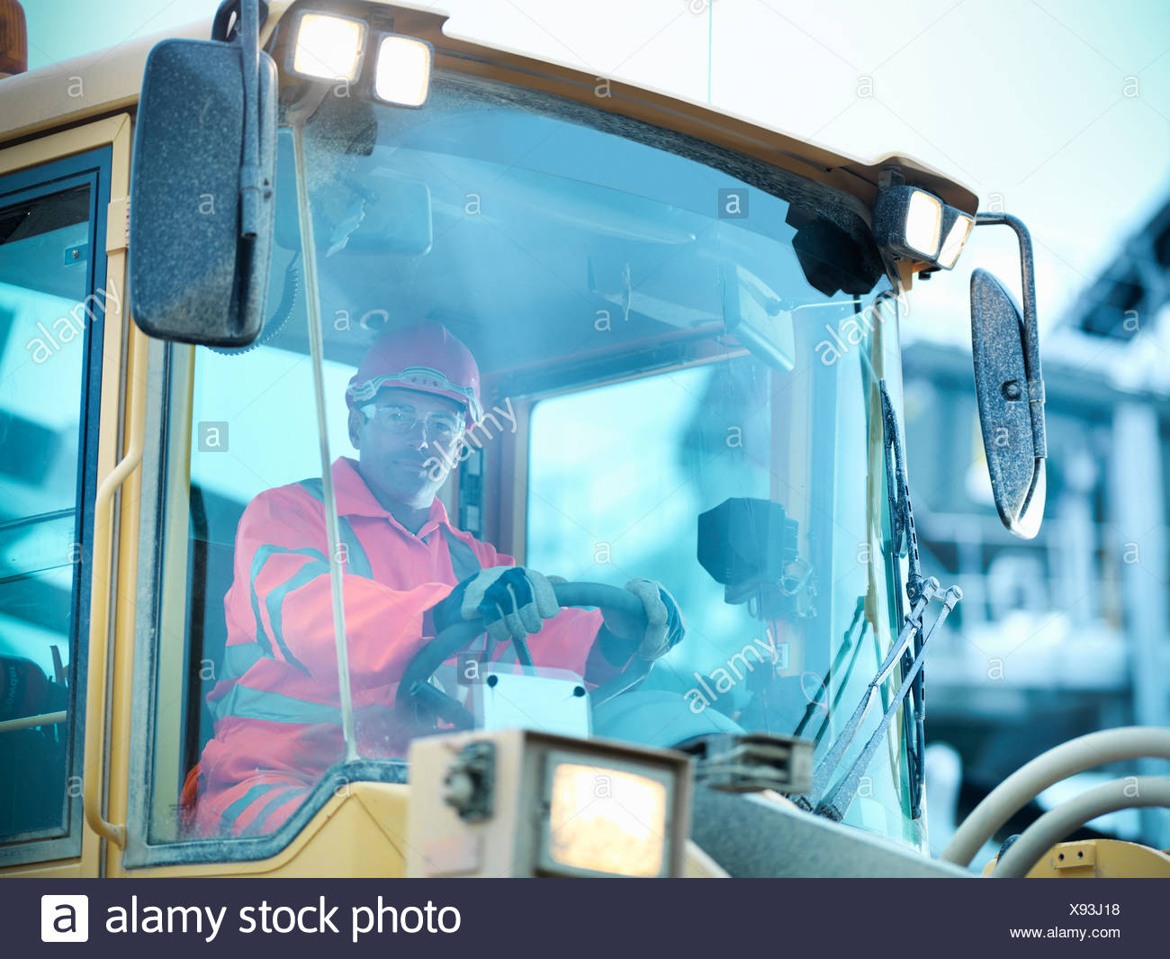 Worker driving industrial digger on site - Stock Image