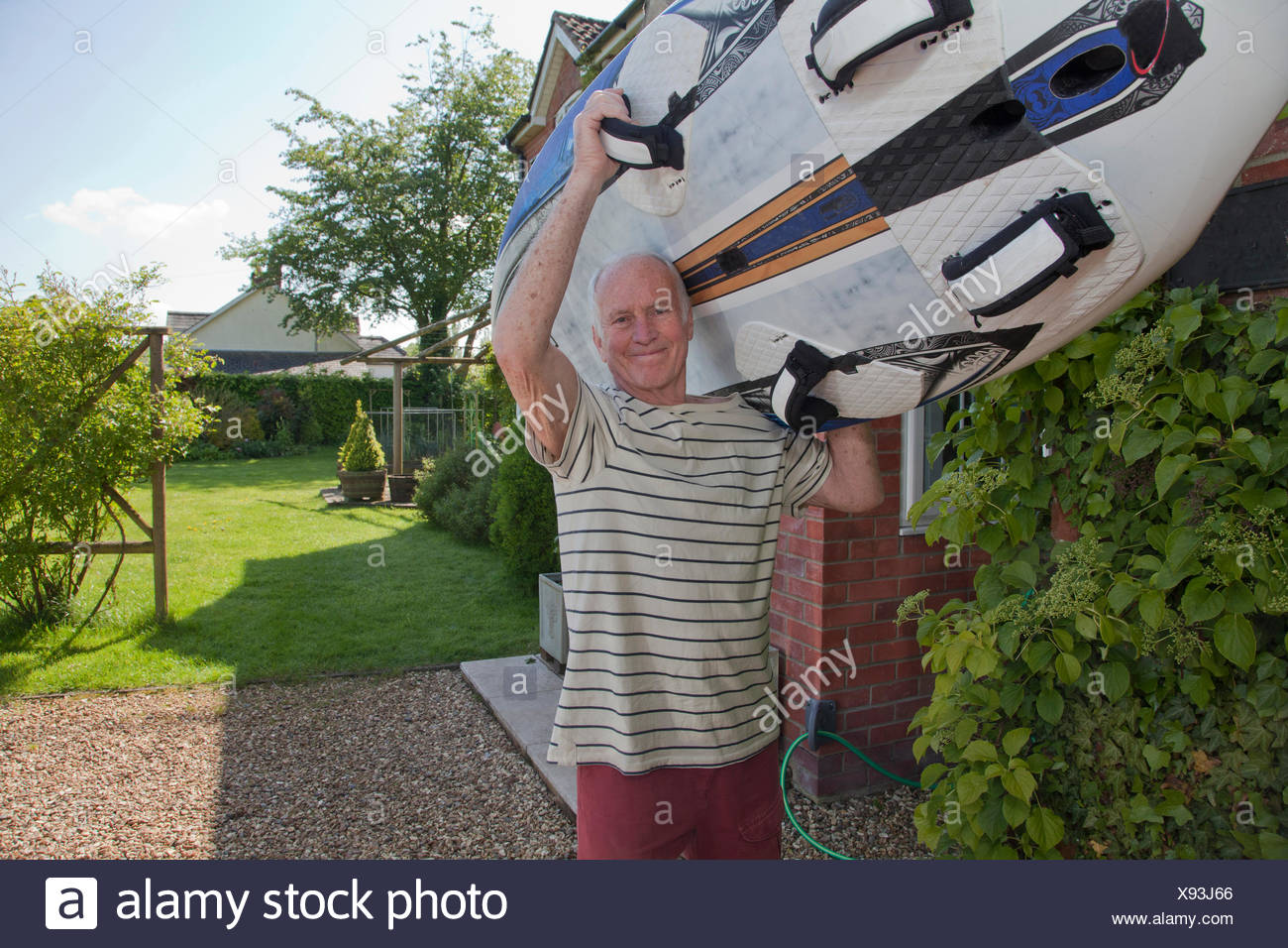 Senior man carrying surfboard - Stock Image
