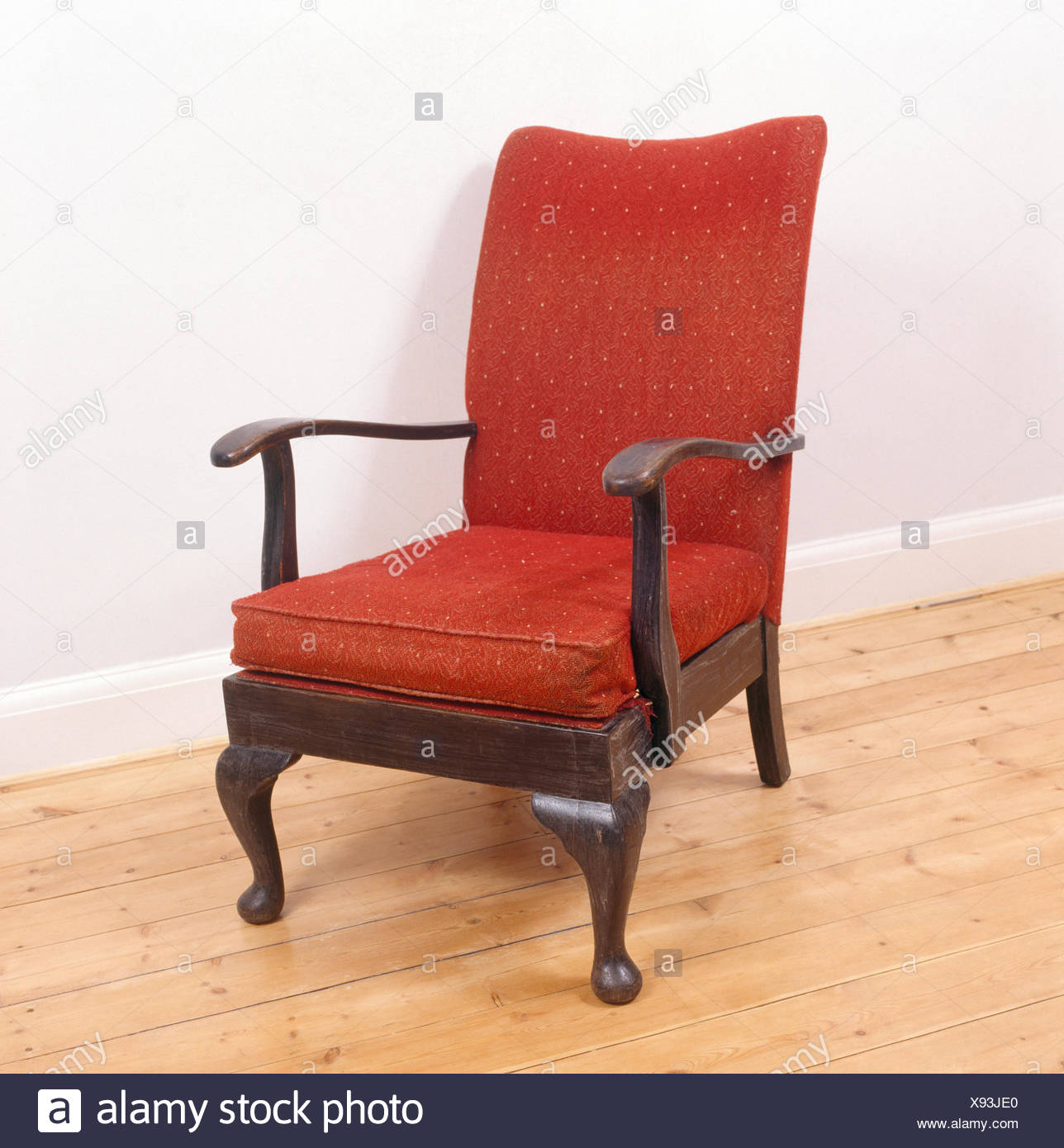 Close-up of old fashioned wood framed chair with red upholstered seat - Stock Image