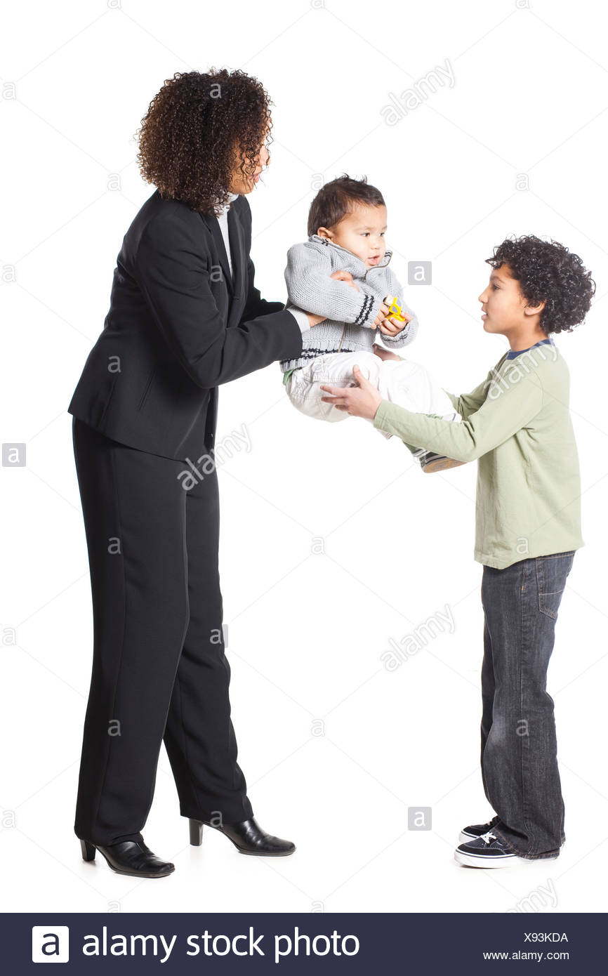Mother passing baby boy (18-23 months) to son (8-9), studio shot - Stock Image