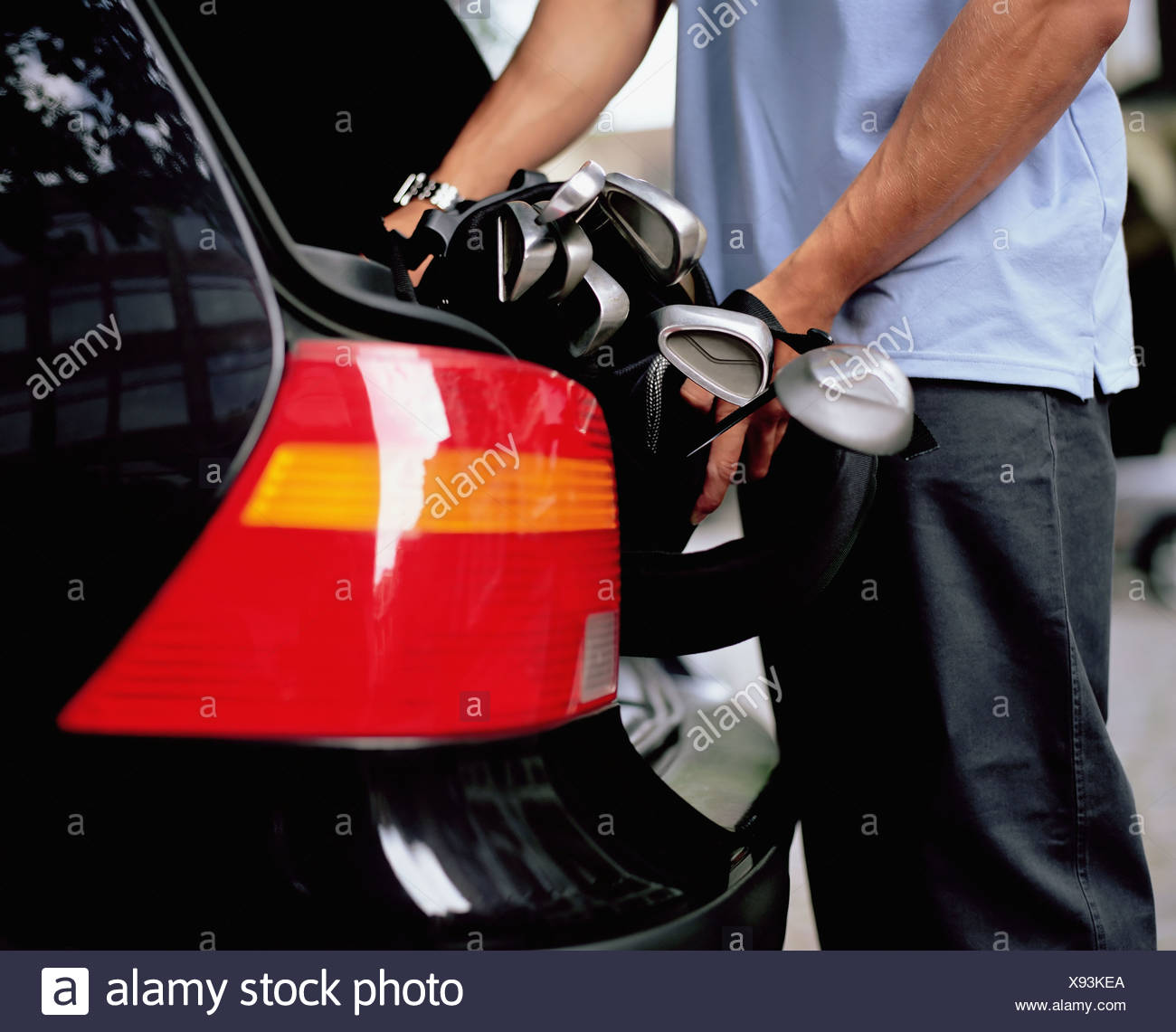 Man putting golf clubs in car boot - Stock Image