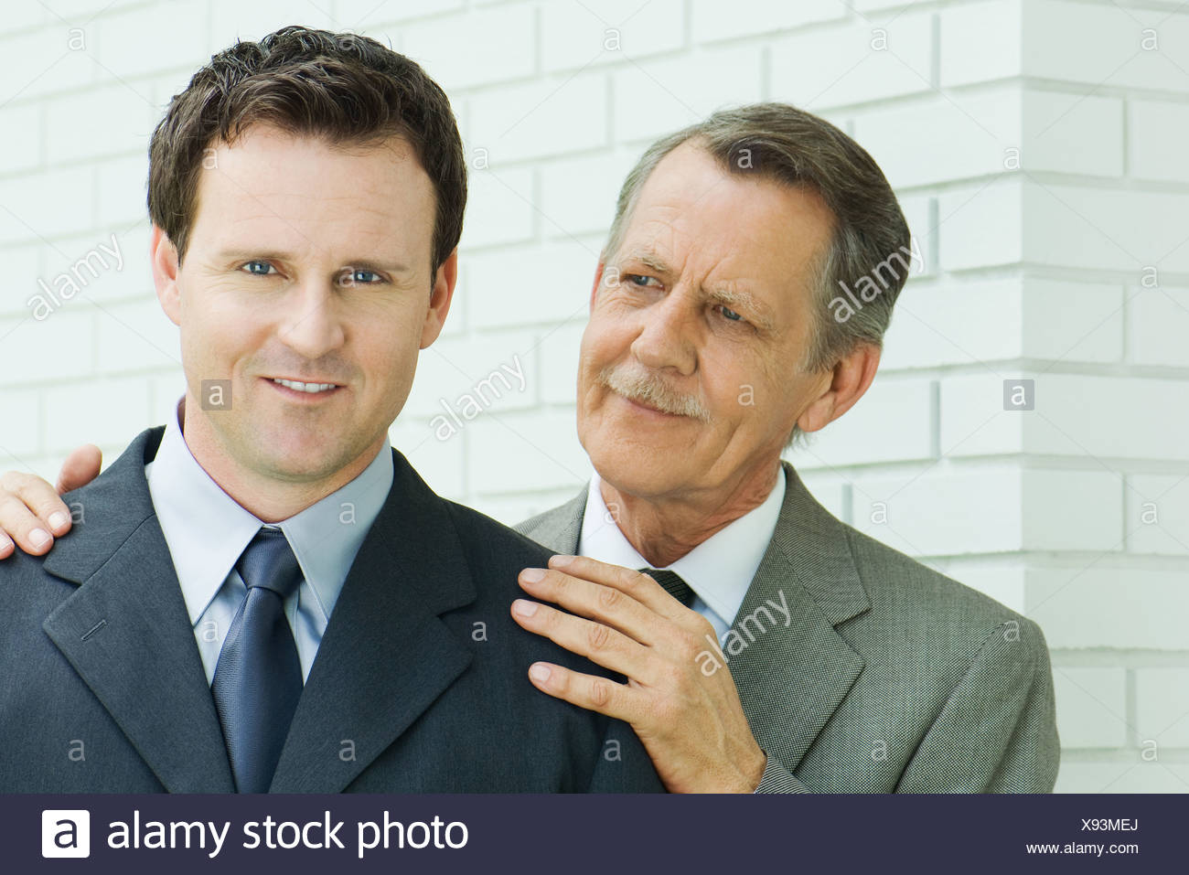 Businessman with hands on younger associate's shoulders, associate smiling at camera - Stock Image