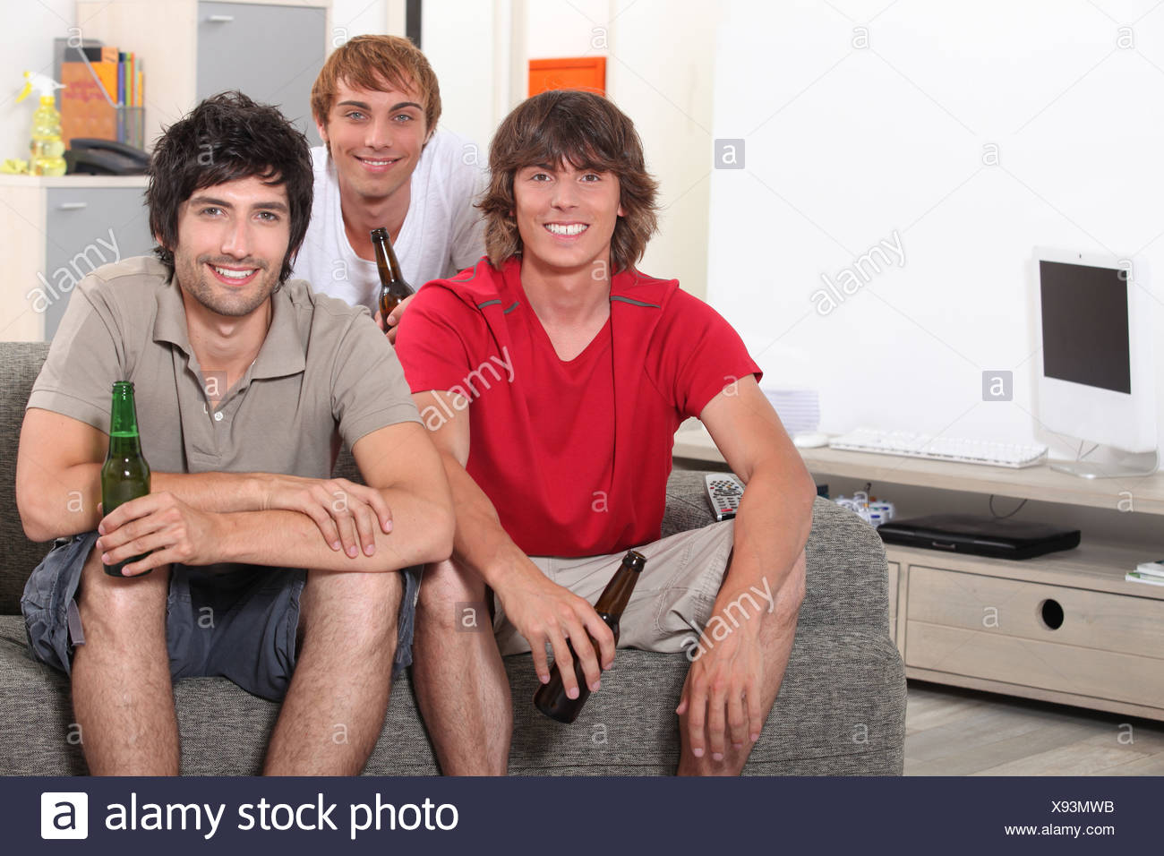 Friends drinking beer at home - Stock Image