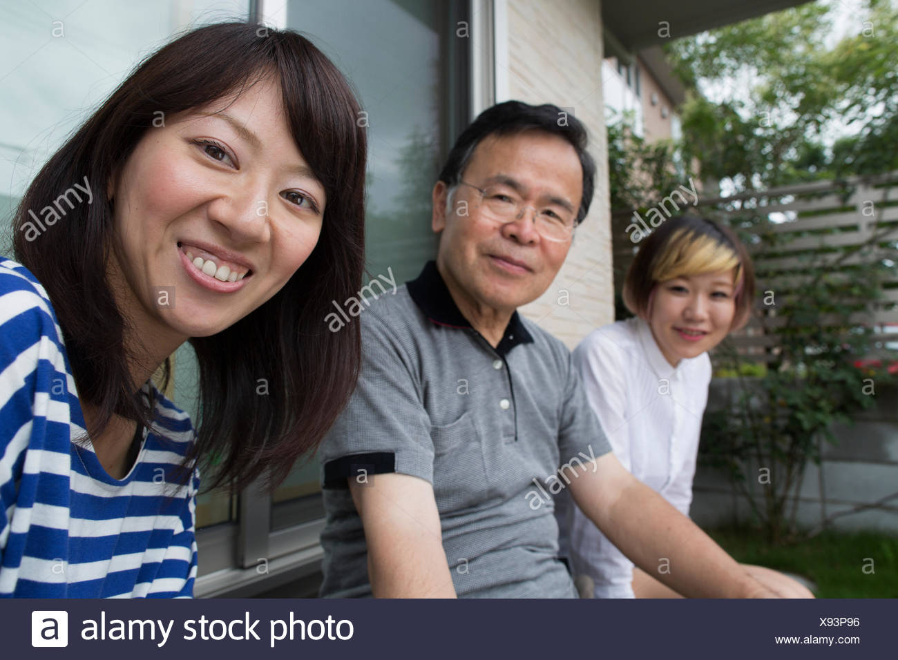 A man and two women sitting at home in a garden. A father and two daughters. - Stock Image