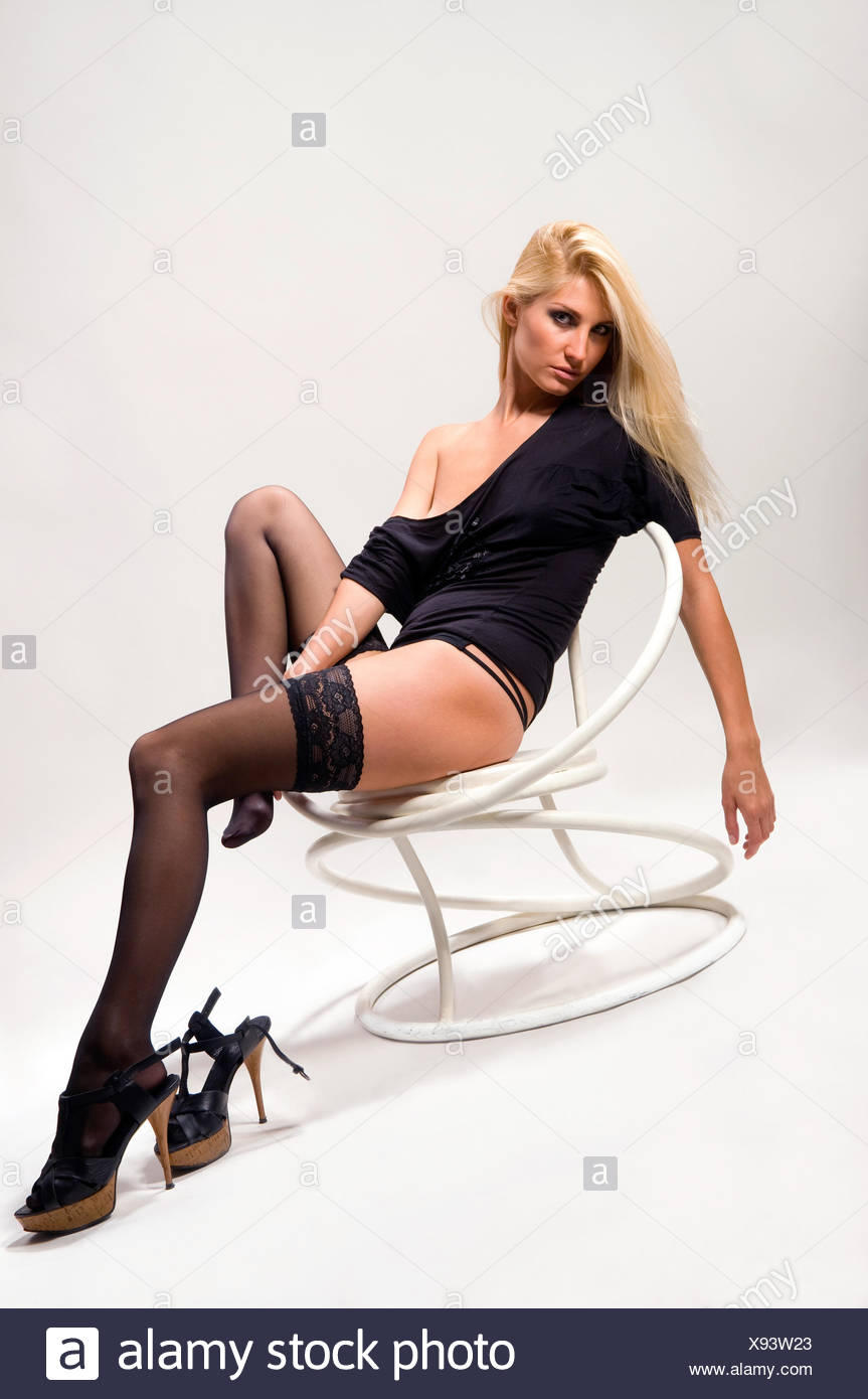 woman sitting on a chair and weeps - Stock Image