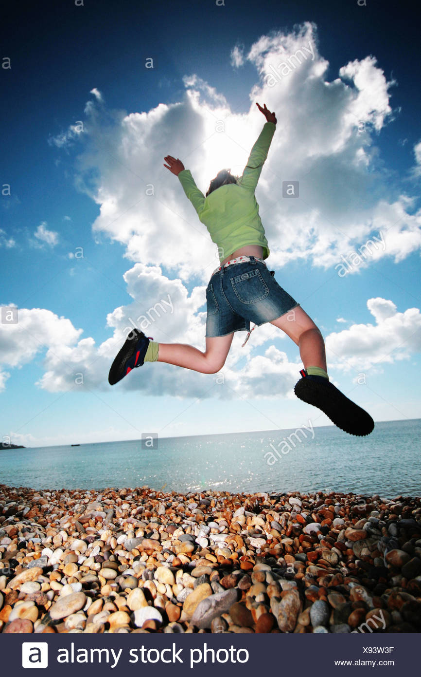 girl leaping on the beach Stock Photo