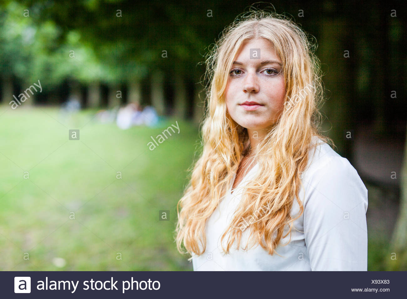 Portrait of beautiful young woman with blond hair in park - Stock Image