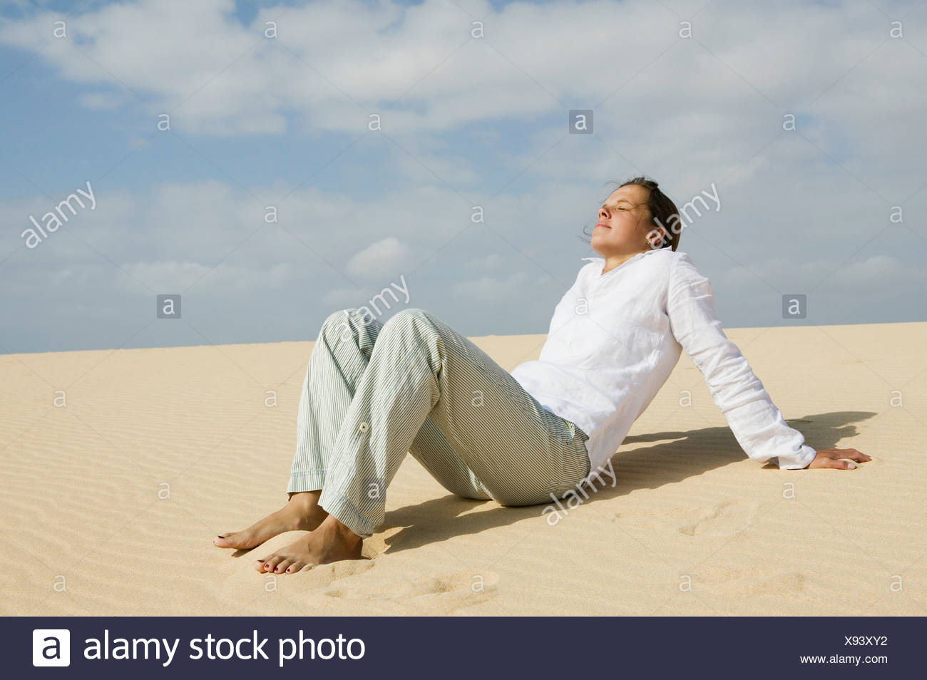 young woman relaxing on sandy beach - Stock Image