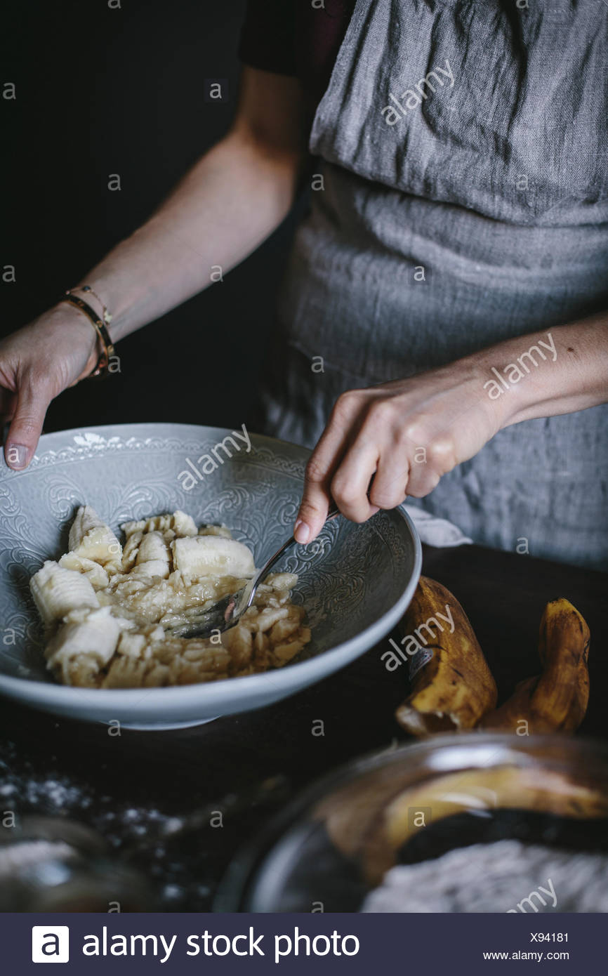 A woman is mashing bananas to be used in a banana bread donut recipe. - Stock Image