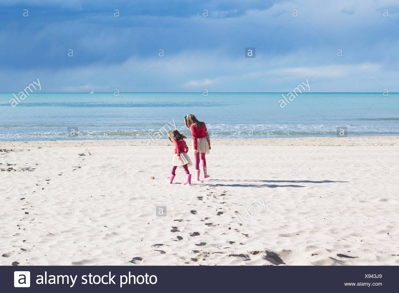 Rear view of two girls walking on the beach - Stock Image