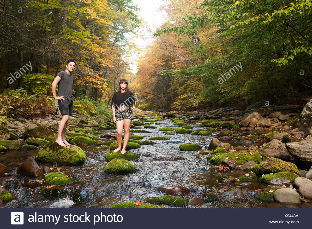 Young couple standing in a mossy stream Stock Photo