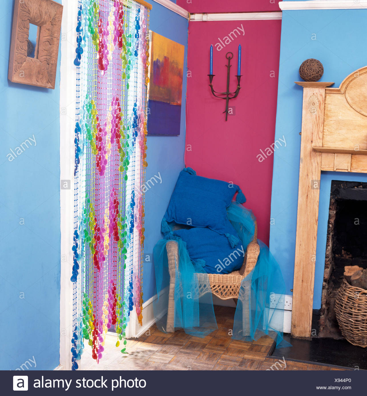Bead curtain on door in blue economy style nineties room with blue cushions on wicker chair - Stock Image