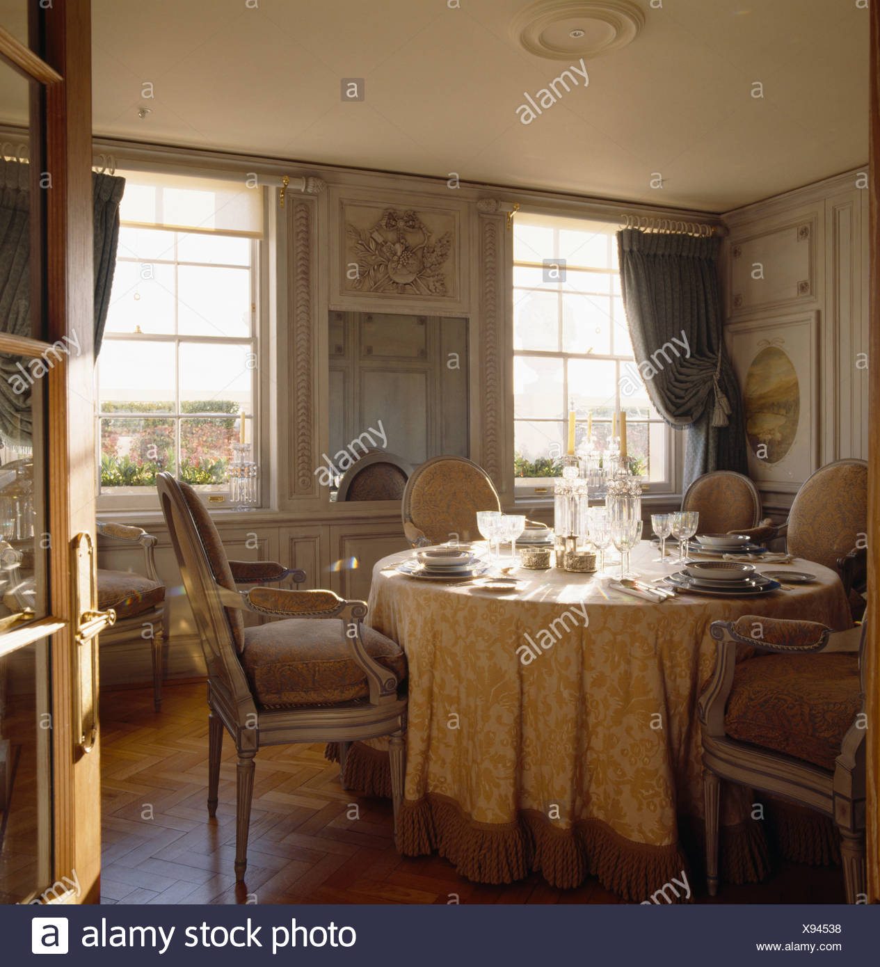 Louis IV style upholstered chairs and table with cream silk cloth in pale grey panelled country dining room - Stock Image