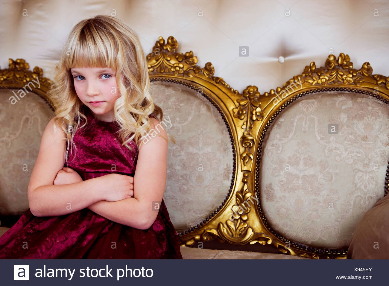 Young girl in a party dress looking bored and unhappy - Stock Image