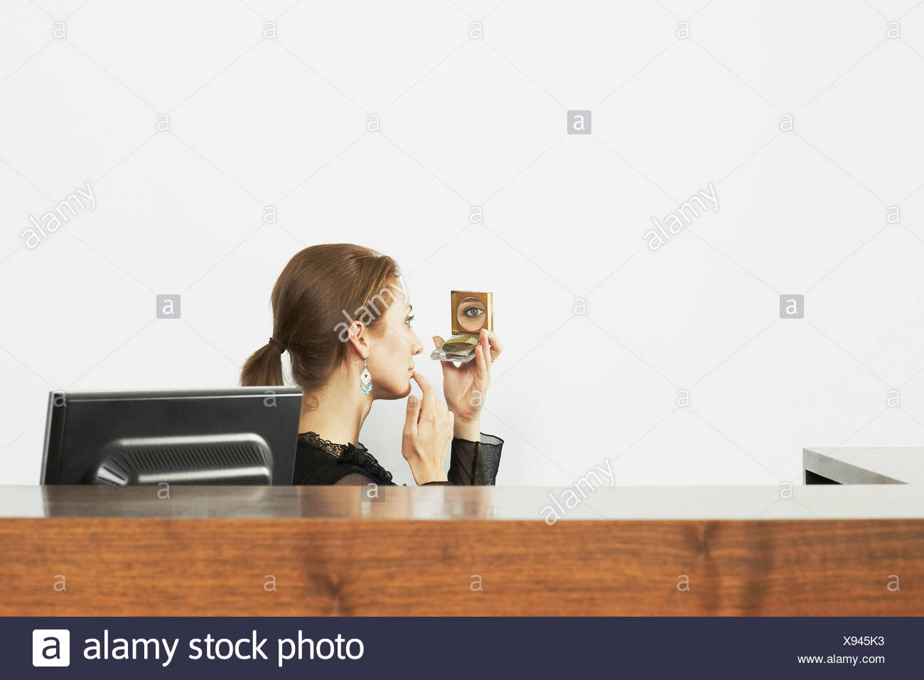 Woman at a desk with a compact mirror - Stock Image