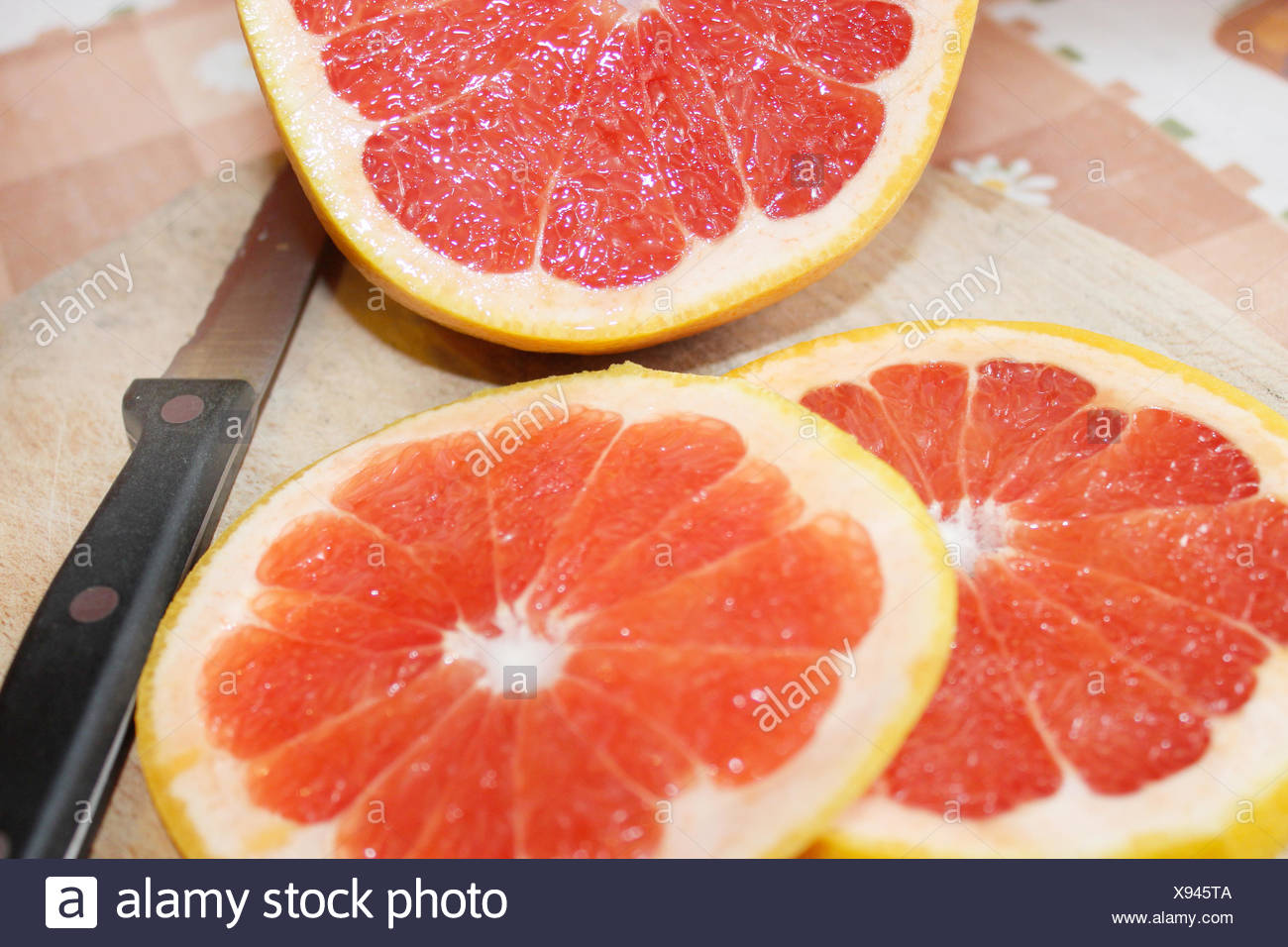 grapefruit bright red and cut by segments - Stock Image