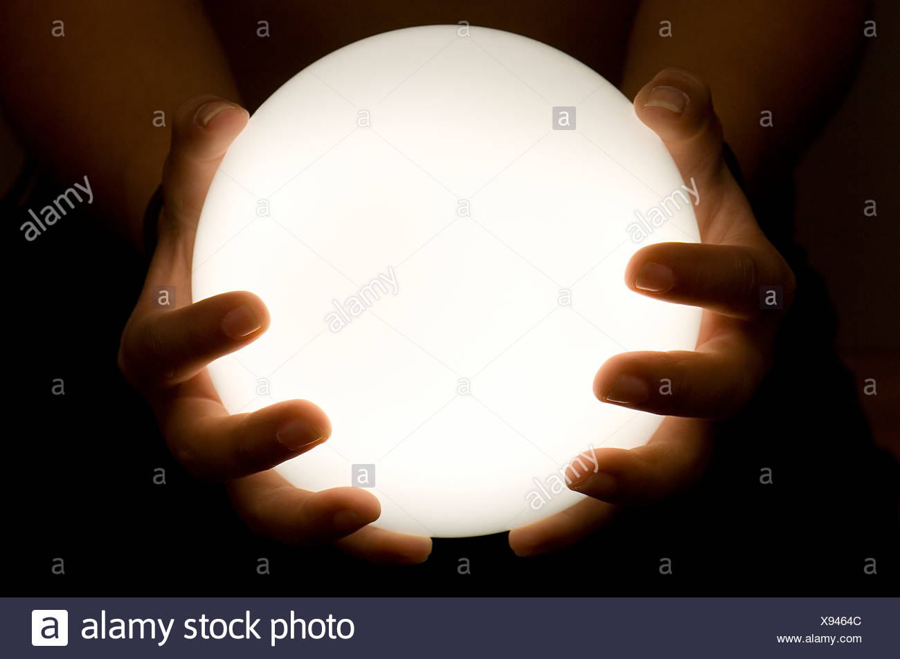Close-up of hands holding luminous ball - Stock Image