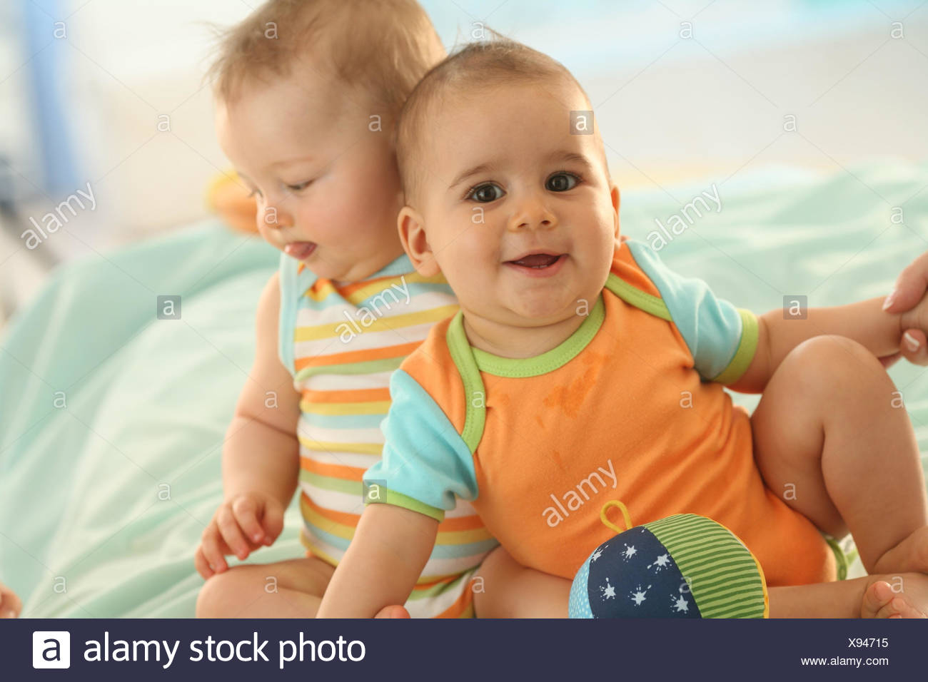 Babies, two, 7 months, smile, play friends, ball, dressed, discoveries, Indoor, boy, laugh, sit, play, toys, portrait, curled, - Stock Image