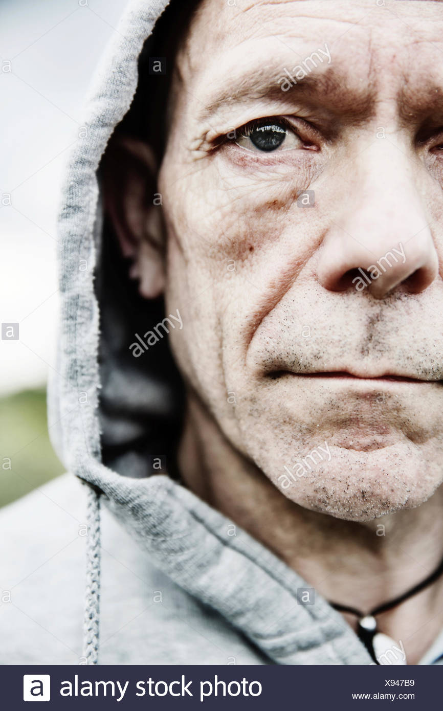 Portrait of pale man wearing hooded jacket, close-up - Stock Image