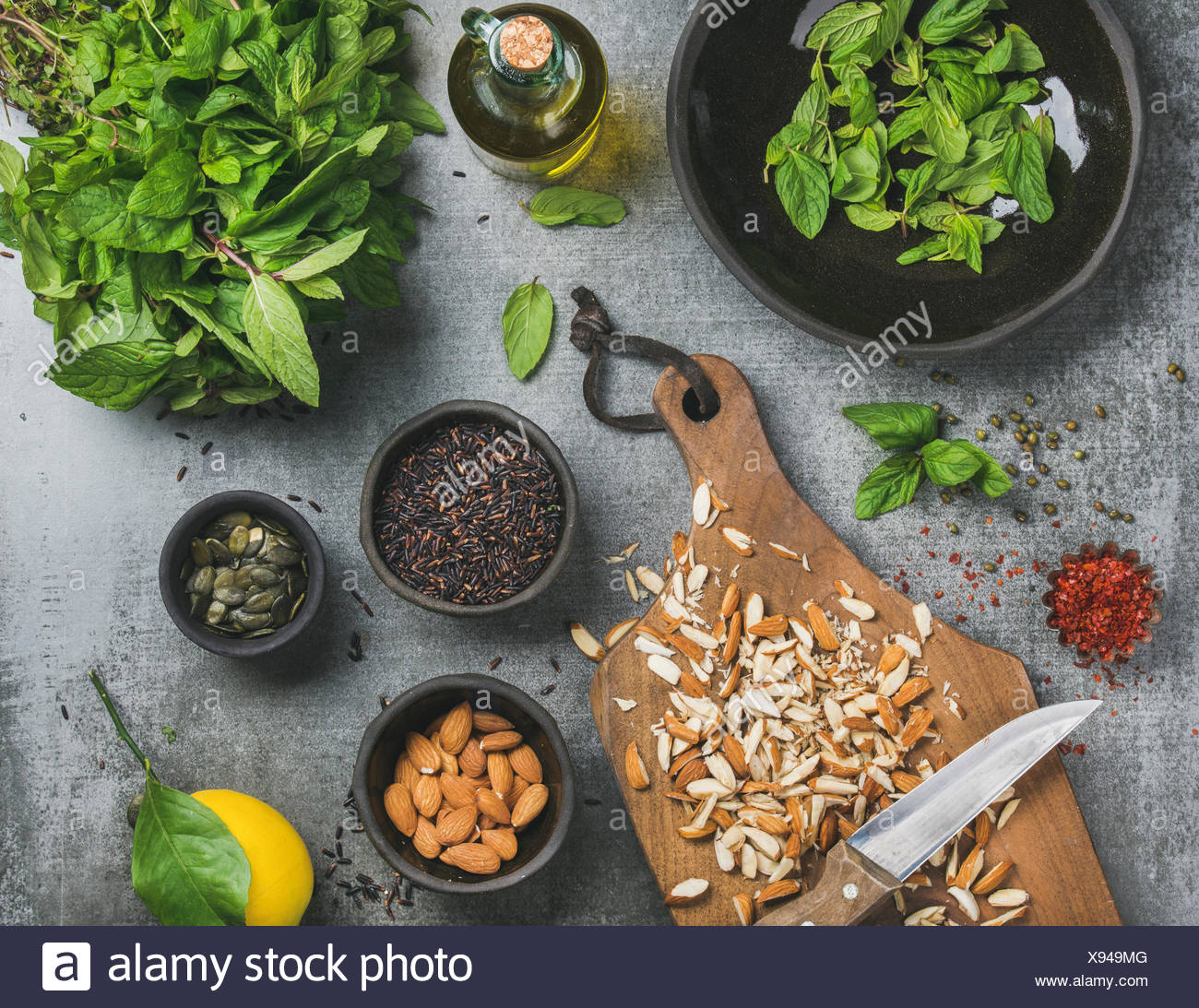 Healthy, vegetarian, vegan or clean eating cooking ingredients. Chopped almonds, fresh mint, oil, black rice, pumpkin seeds spices, lemon over grey co - Stock Image
