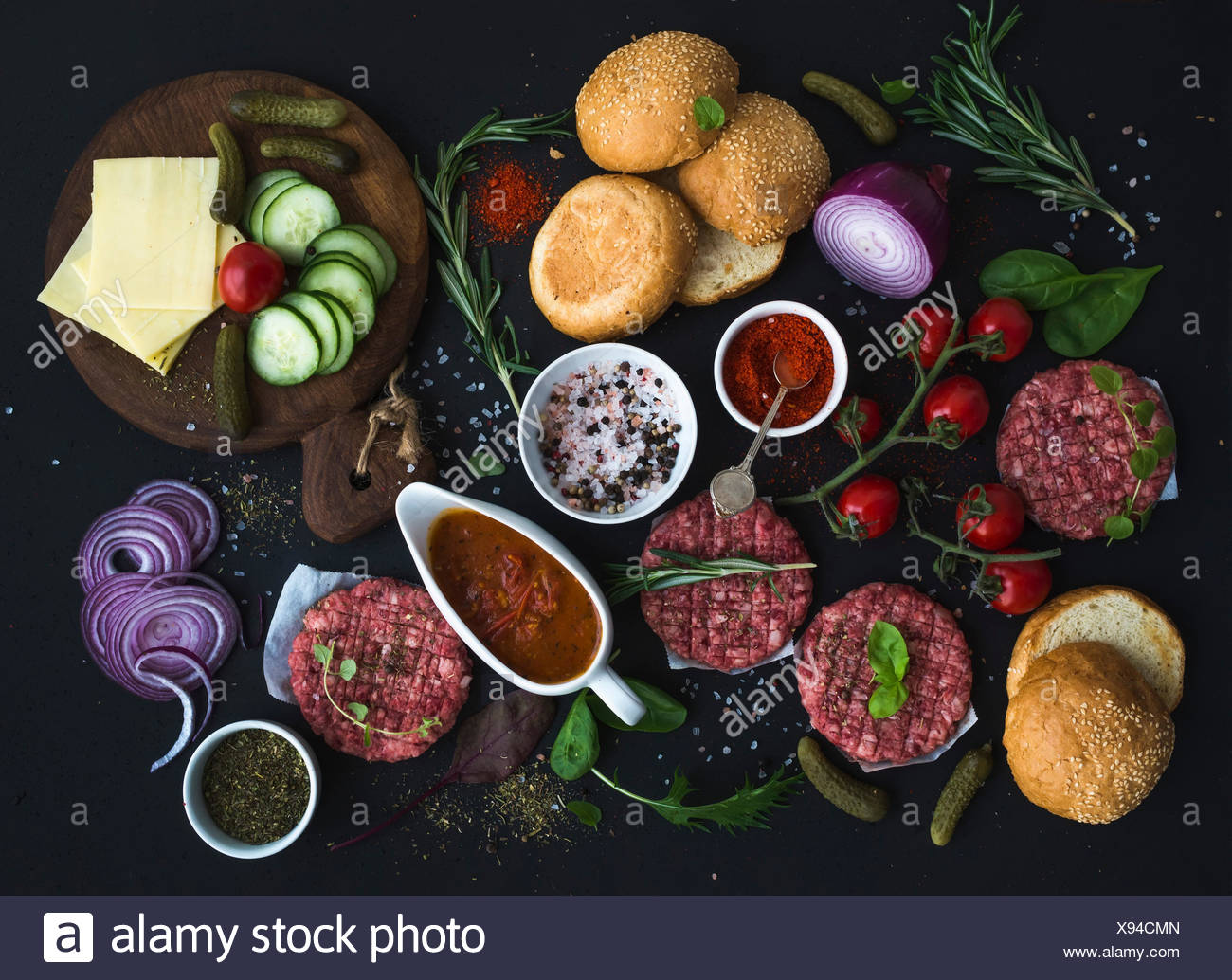 Ingredients for cooking burgers. Raw ground beef meat cutlets, buns, red onion, cherry tomatoes, greens, pickles, tomato sauce, - Stock Image