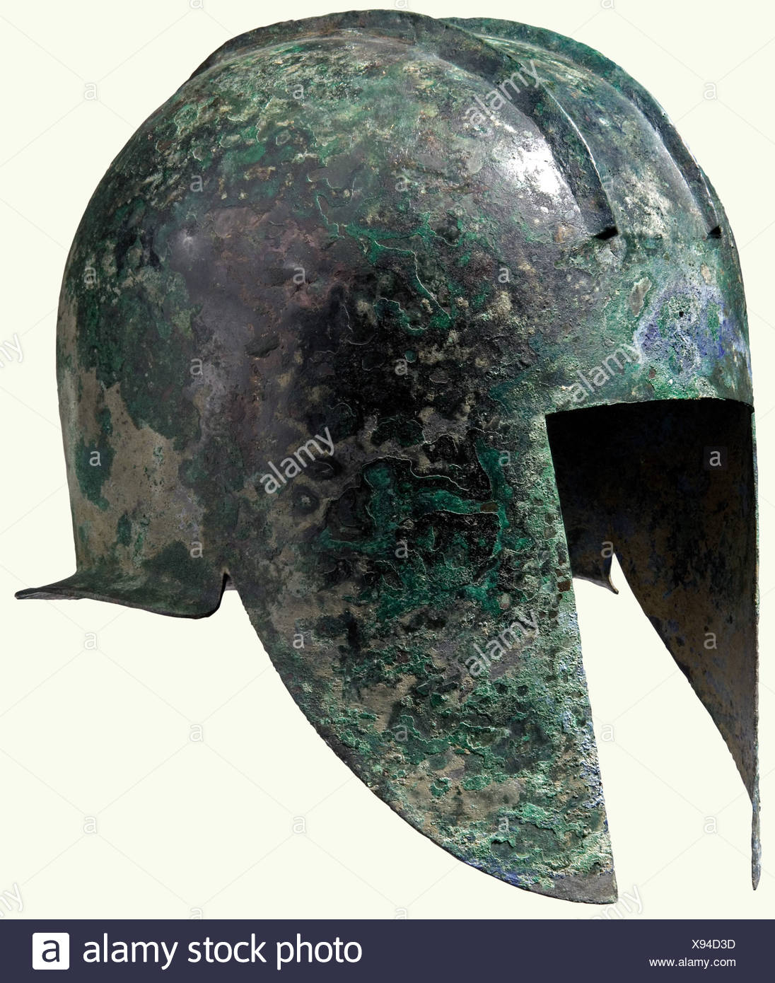 An Illyrian helmet, 5th century B.C. Bronze with greenish patina. High embossed skull with position for the crest between two ridges. Long cheek pieces coming to a point. Neck protector with a short, angled rim. Holes and solder remnants from the original attachment of helmet decorations at the brow and nape. There is a well-restored crack toward the top of the skull. Height 22.5 cm. Weight 962 grams. historic, historical, ancient world, ancient world, ancient times, object, objects, stills, clipping, cut out, cut-out, cut-outs, Additional-Rights-Clearances-NA - Stock Image
