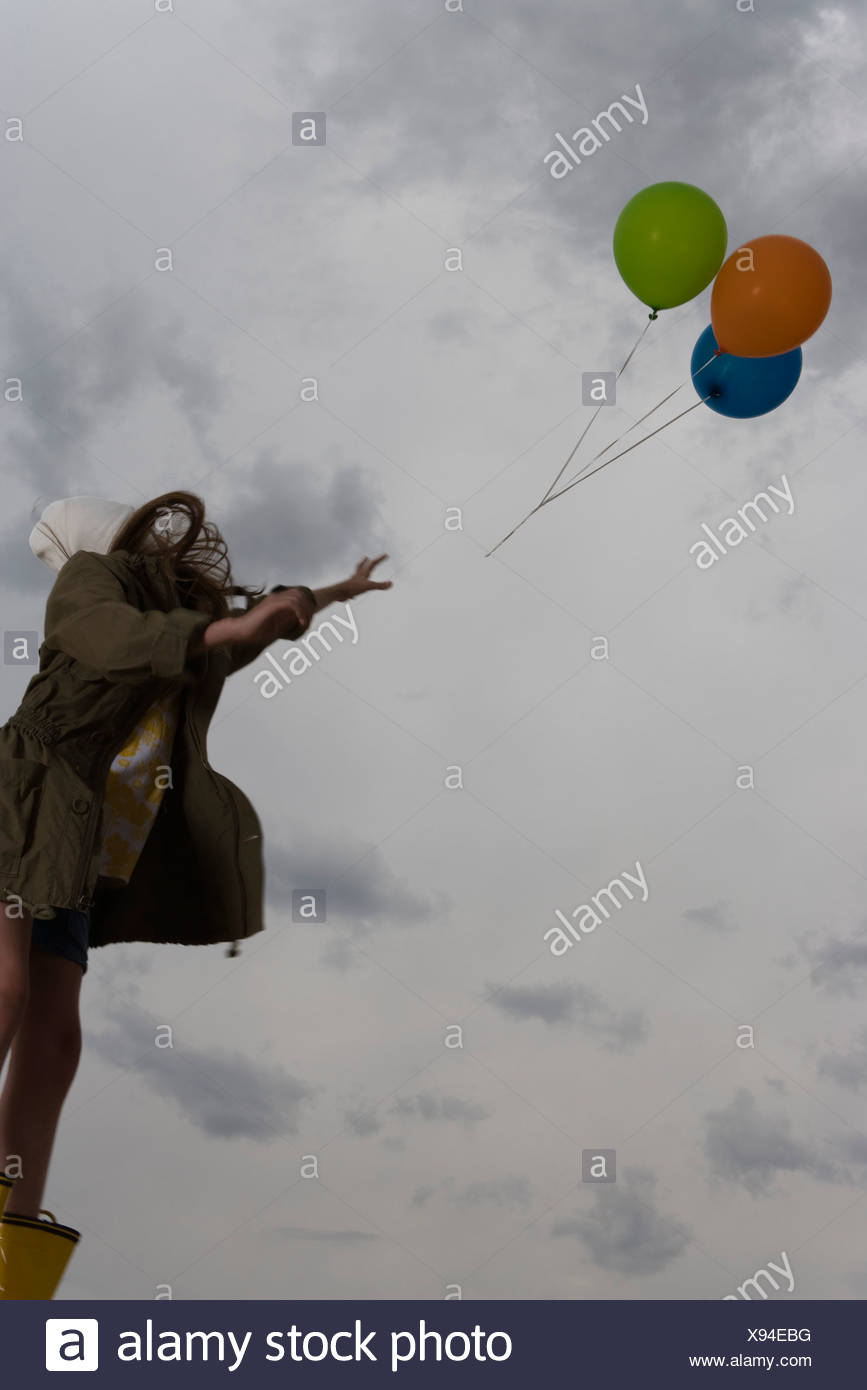 Female watching as bunch of balloons float away up into cloudy sky - Stock Image