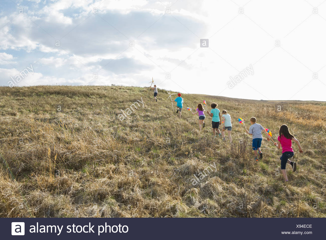 Kids walking up hill with pinwheels and windmills - Stock Image