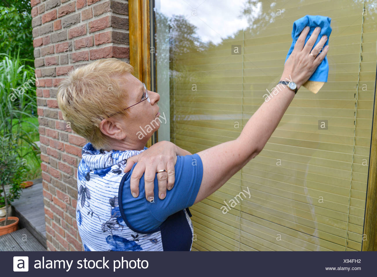 Woman with joint pain in her shoulder cleaning a window - Stock Image