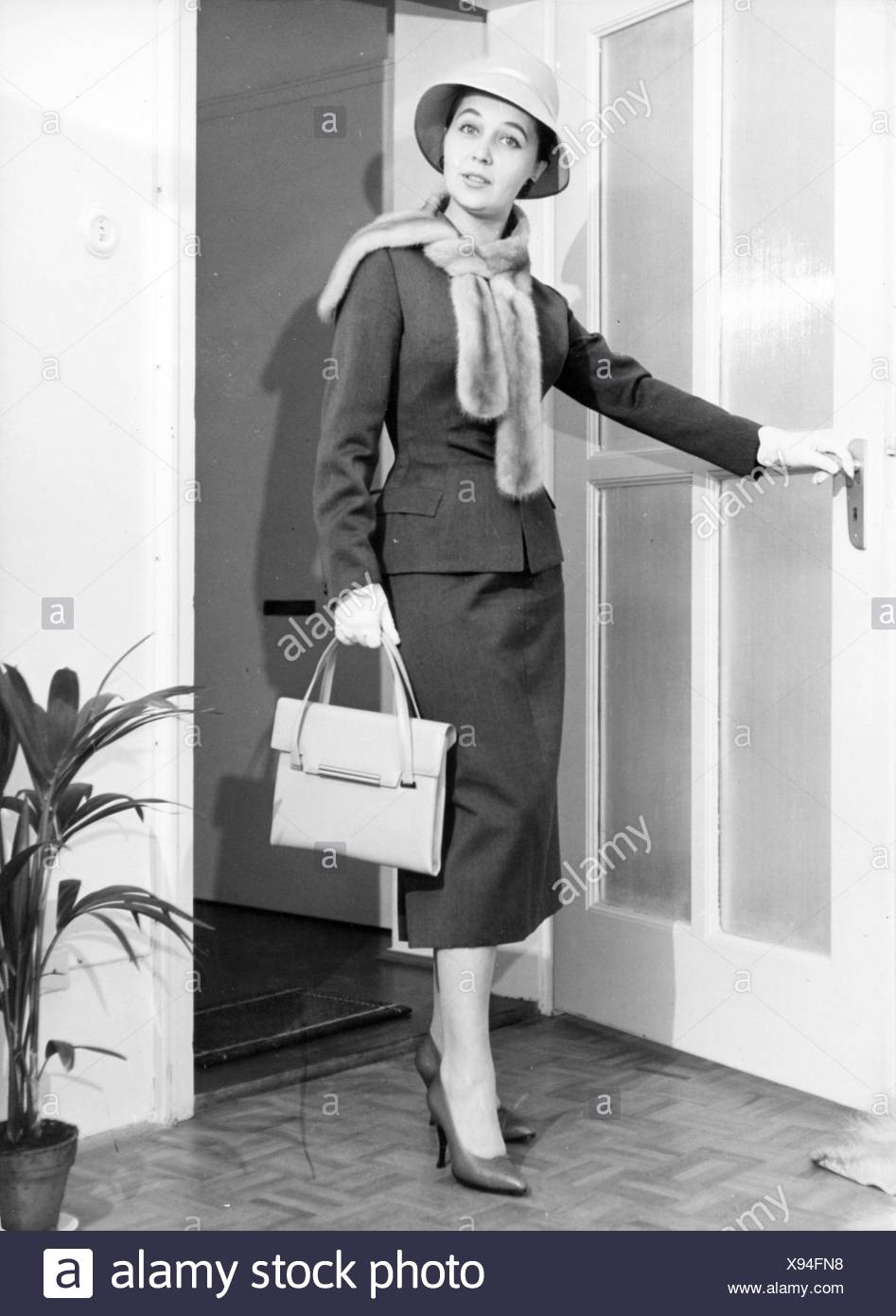 fashion, 1950s, Young woman in woman's suit by Barbara Benkö, 1957, Munich, 1957, 20th century, 50s, Germany, clothes, outfit, outfits, ladies' fashion, woman's suit, costume, costumes, headpiece, headpieces, hat, hats, fur stole, stole, fur, furs, handbag, pocketbook, purse, handbags, pocketbooks, purses, bag, bags, ladies' shoes, fashion for women, women's clothing, mannequin, fashion model, mannequins, fashion models, fashion, posture, posing, pose, door, doors, woman, women, historic, historical, woman, women, female, people, Benkoe, Benkö, Benko, Additional-Rights-Clearences-NA - Stock Image
