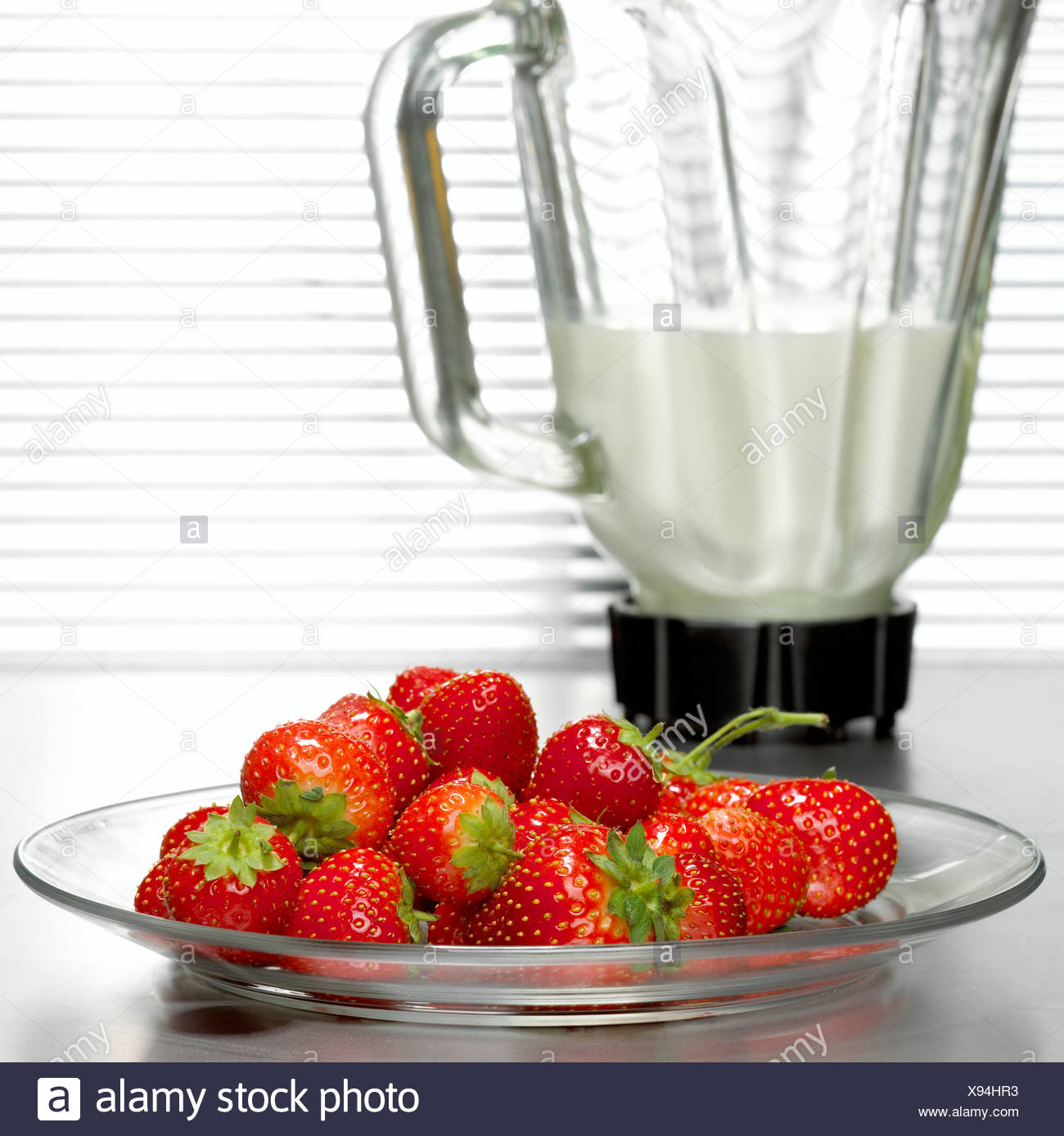 Strawberries in front of mixer, close-up - Stock Image