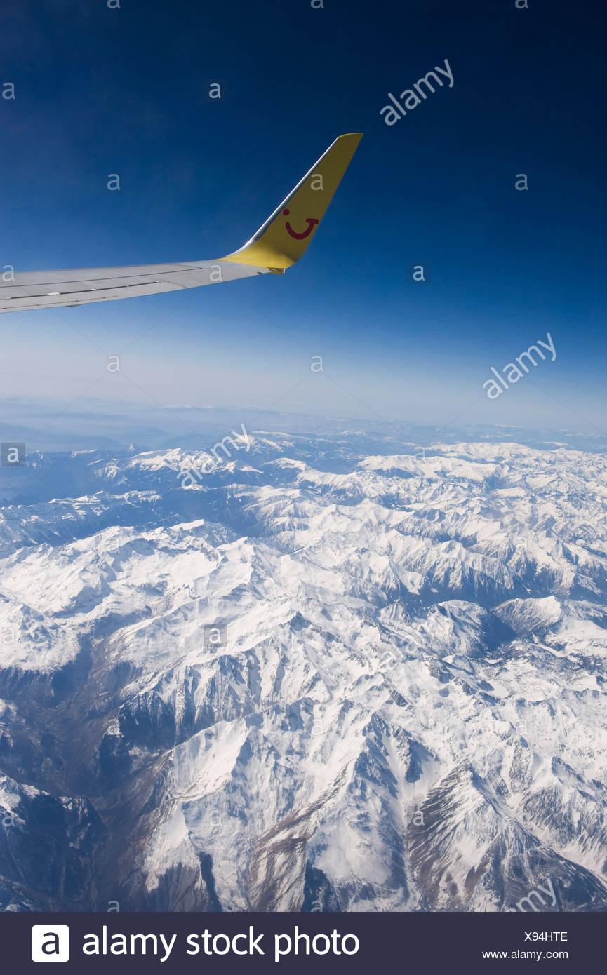 Flight above the Alps, aircraft wing with winglets, Europe - Stock Image
