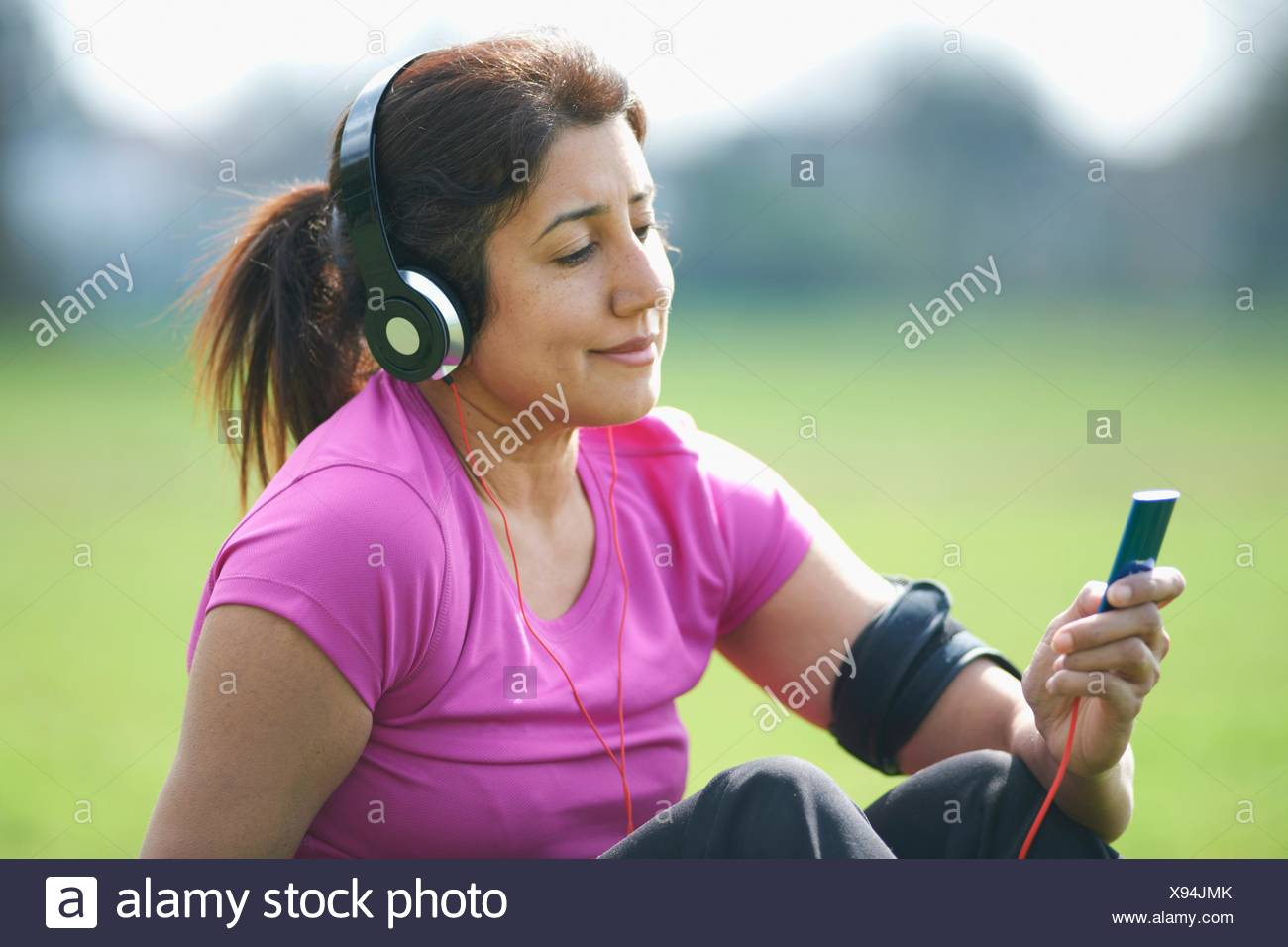 Mature woman taking exercise break in park selecting music from MP3 player - Stock Image