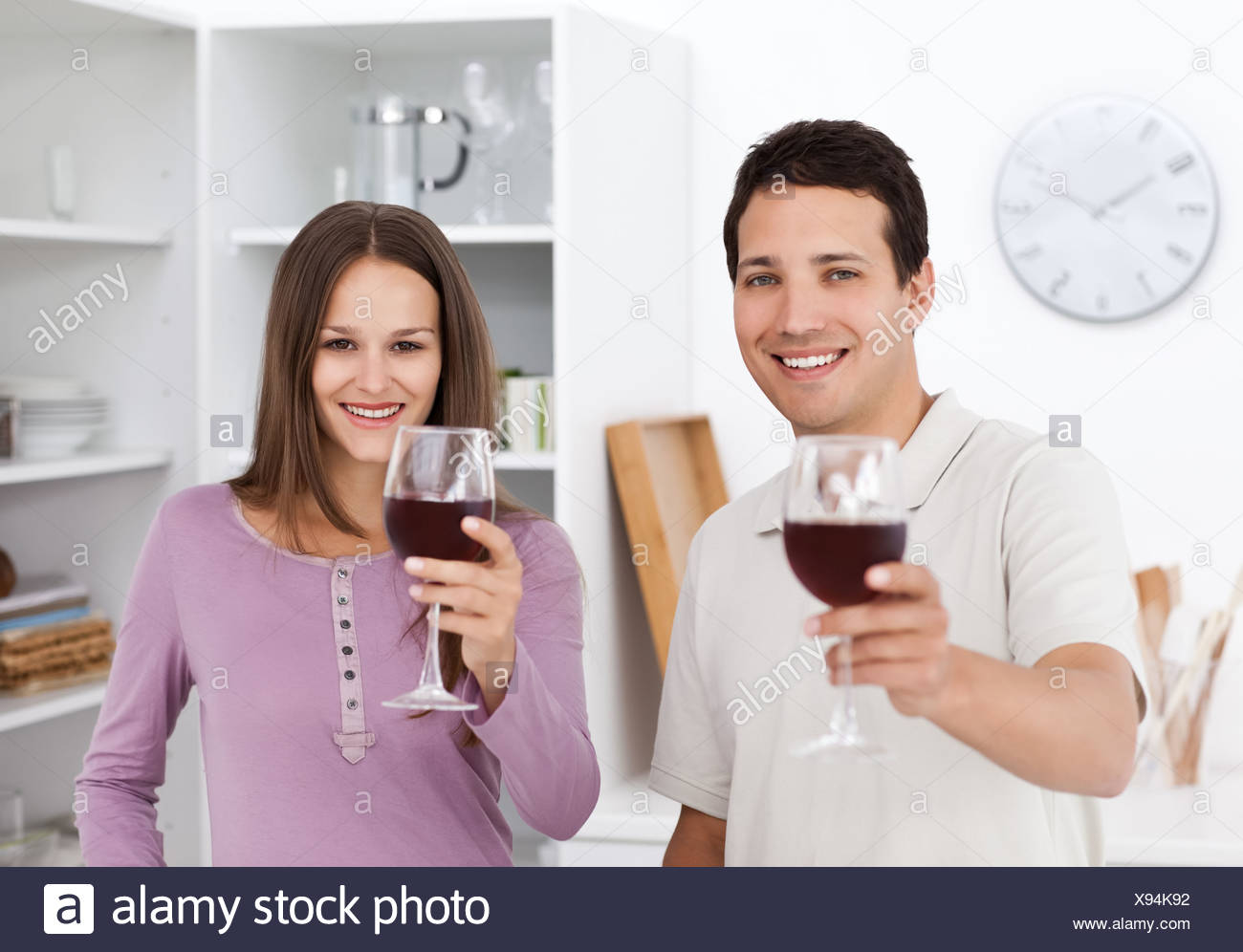 Young couple toasting with glasses of red wine - Stock Image