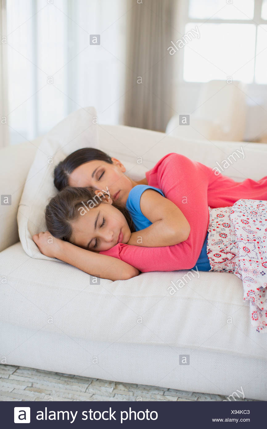 Mother and daughter napping on sofa in living room Stock Photo