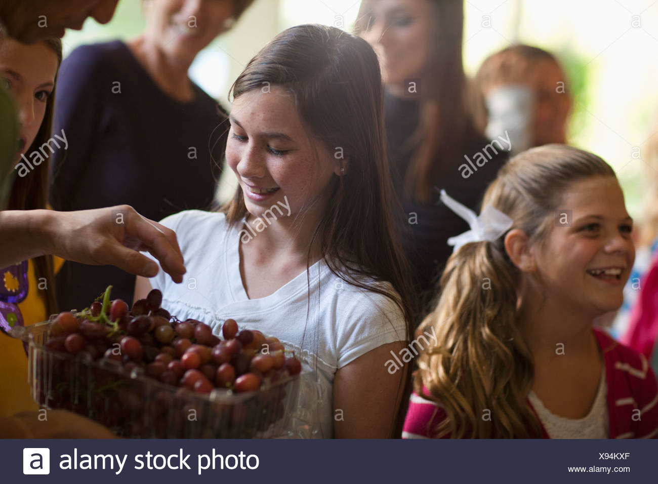 Girls (10-11, 14-15) and family during celebration event - Stock Image