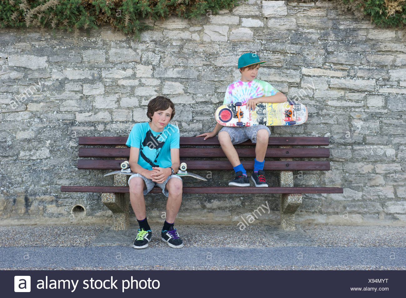 Portrait of two boys sitting on bench holding skateboards - Stock Image
