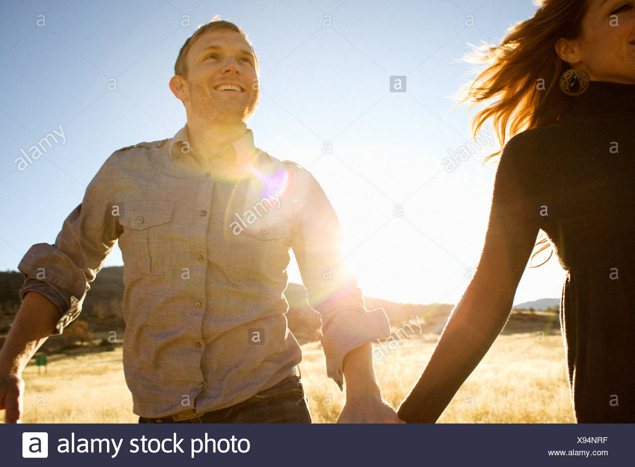 Couple run while holding hands and smiling in an open field. - Stock Image