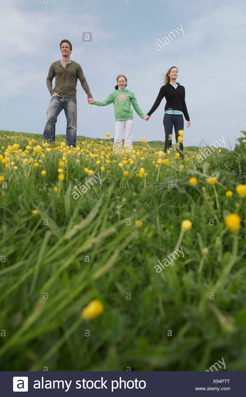 Parents and child stand on hillside - Stock Image