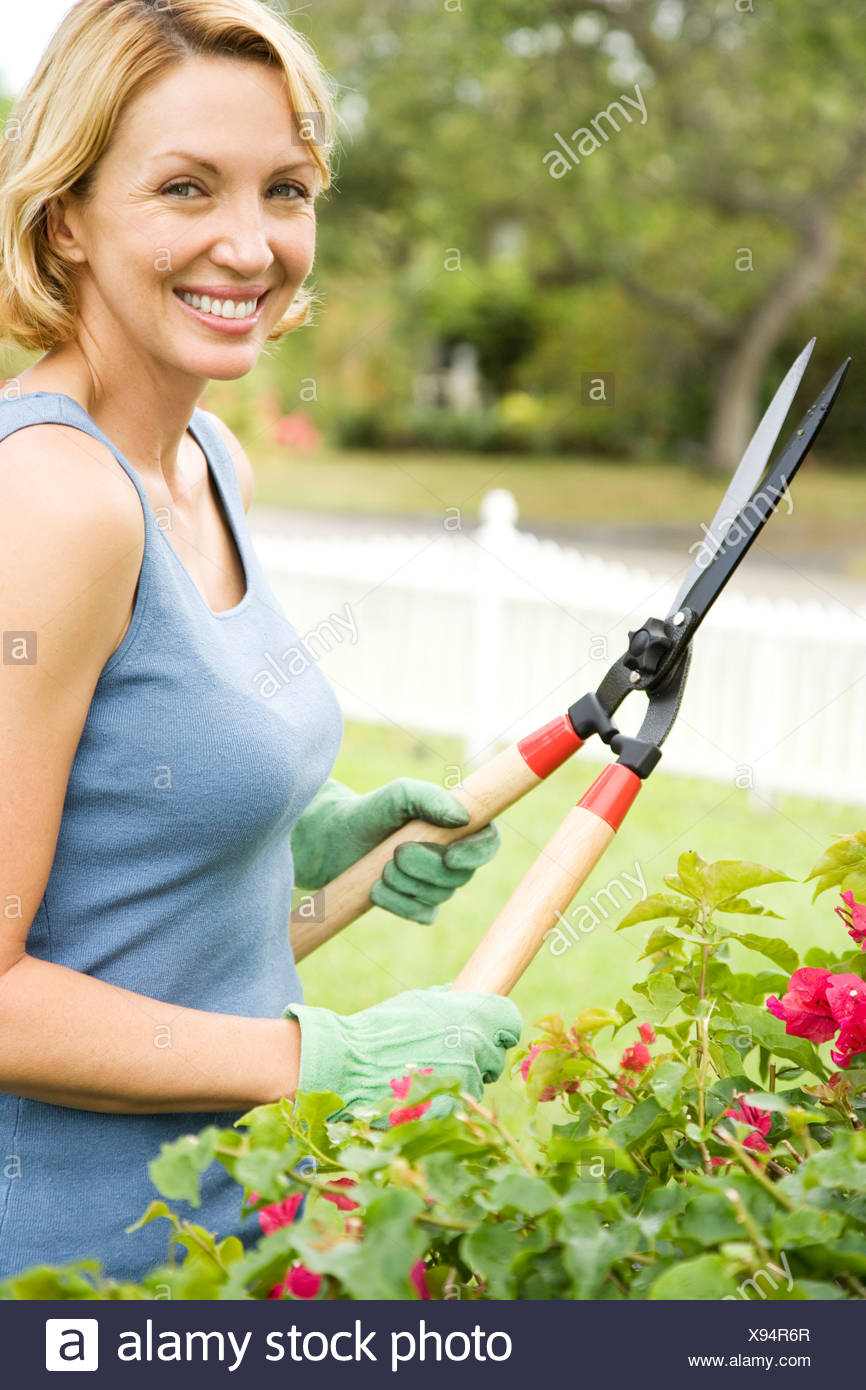 woman in the garden holding garden shears - Stock Image