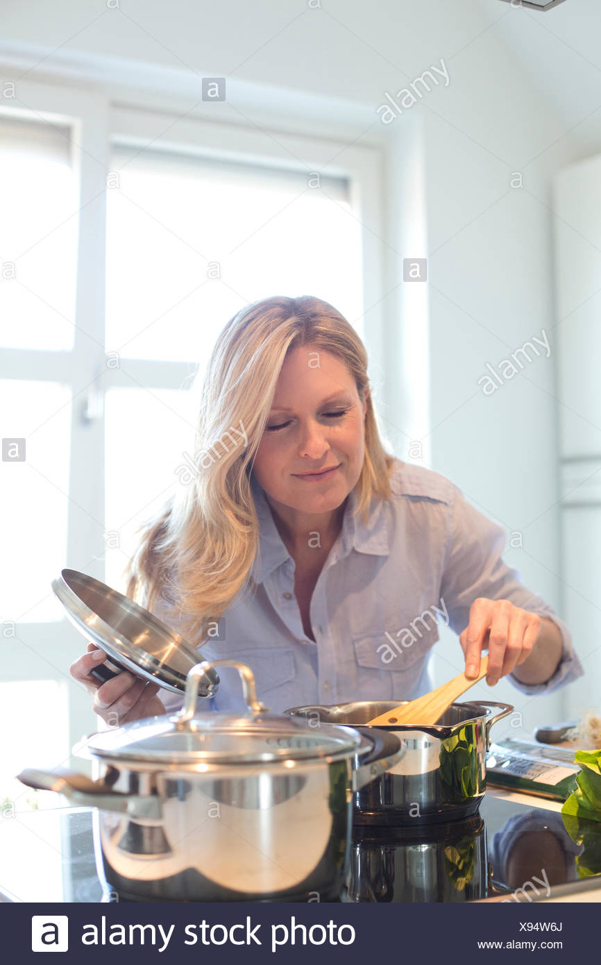 Woman cooking in kitchen enjoying smell from cooking pot - Stock Image