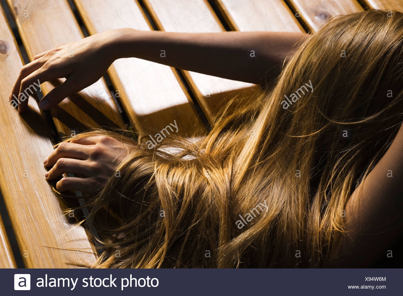 Woman lying face down on floor, long hair covering arm, cropped - Stock Image