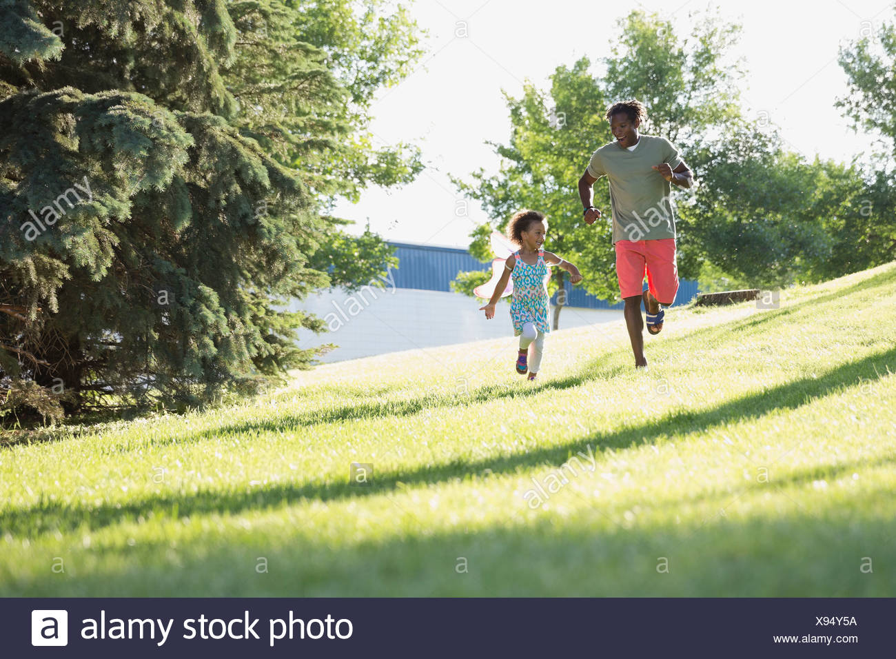Cheerful father and daughter running in park Stock Photo