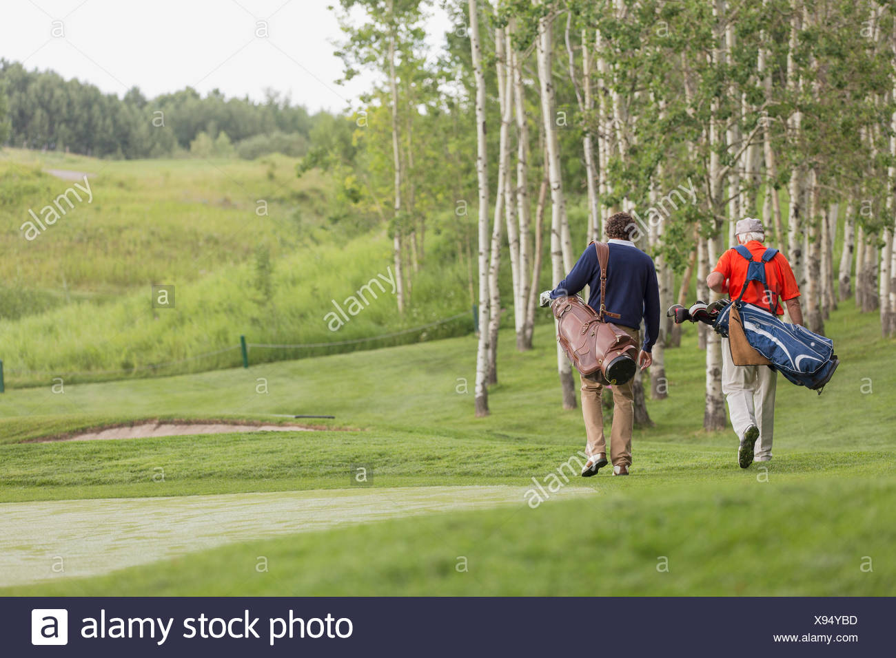 view from behind of golfers walking off tee - Stock Image