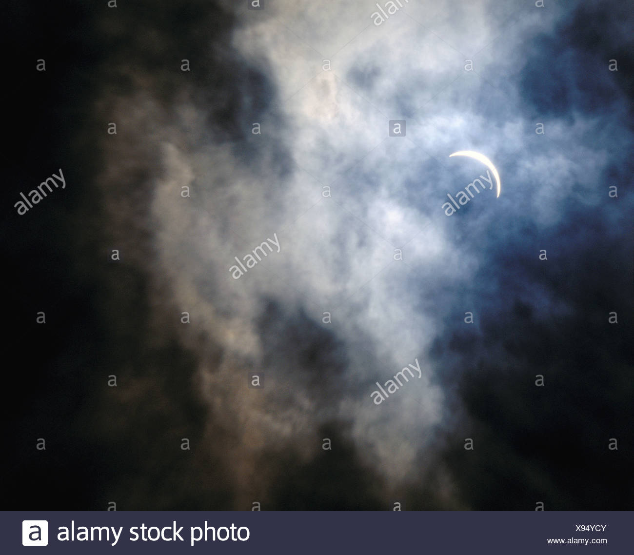 behind clouds in 1999 sickle cresent solar darkness darkness sun - Stock Image