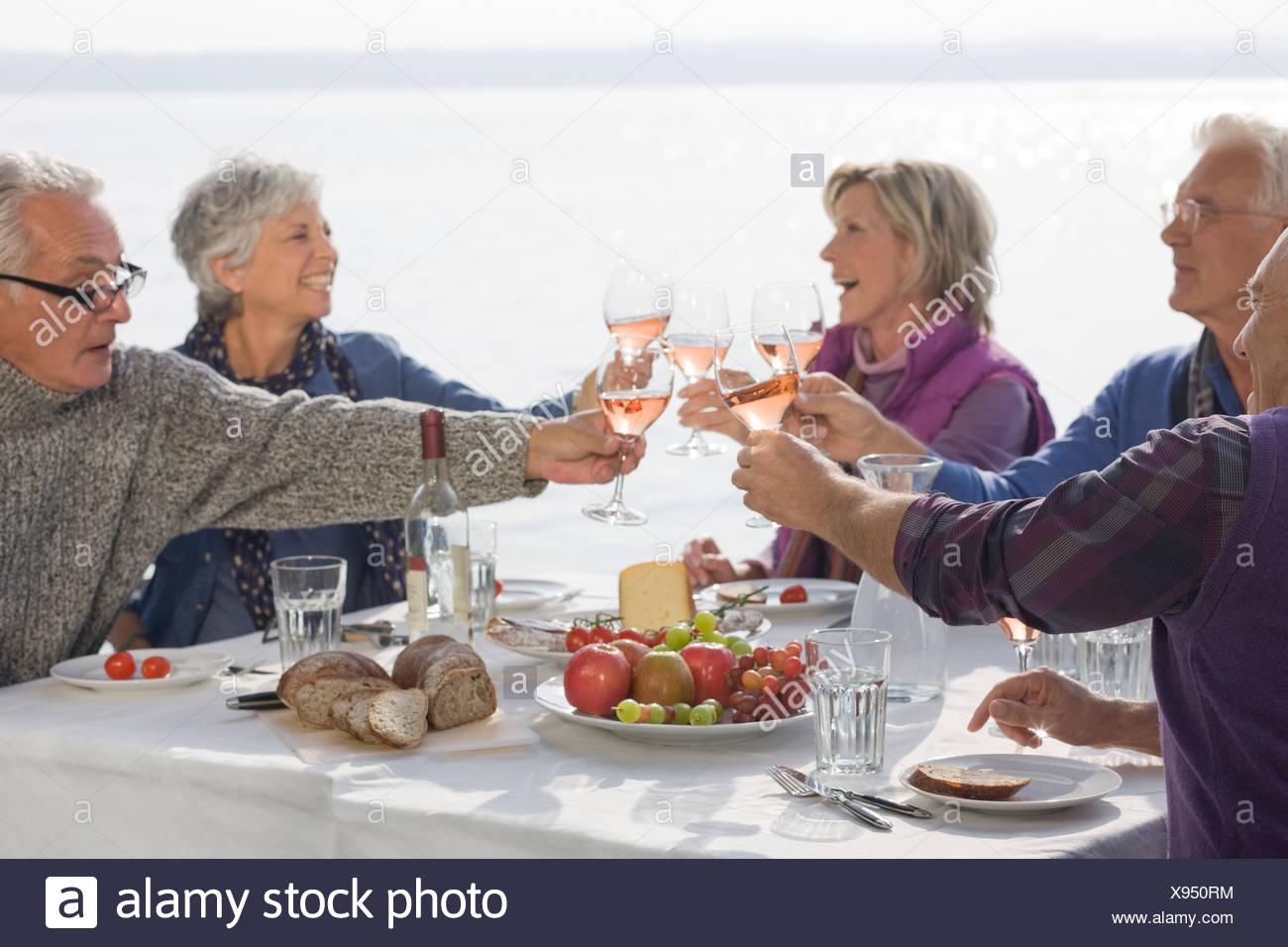 Five senior friends having lunch, raising their glasses - Stock Image