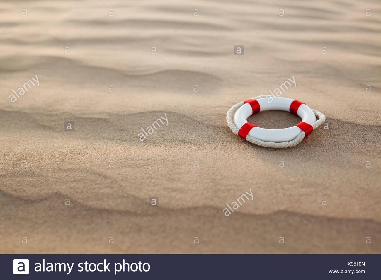 Lifebuoy in desert Stock Photo