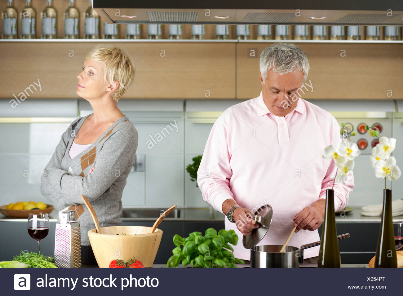 Blond woman turned away from a man who is cooking - Stock Image